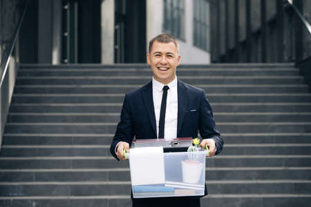 Portrait male office worker with box of personal stuff. Businessman lost job. Man outdoors. Jobless person. Unemployment concept. Left without money
