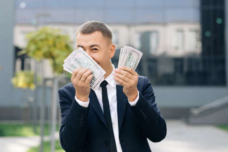 Man shows money and celebrating success, victory while looking to camera. Outdoors. Amazed happy excited businessman with money - U.S. currency dollars banknotes