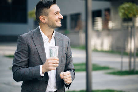 Happy rich successful man holds dollars outdoors. Portrait of satisfied businessman holds money. Lifestyle, richness, joy, success