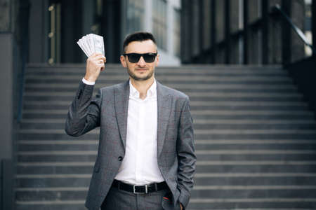 Lifestyle, richness, joy, success. Happy rich successful man holds dollars outdoors. Portrait of satisfied businessman holds money.