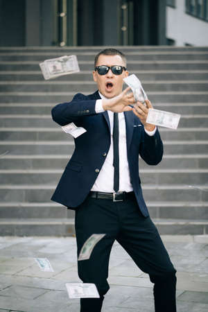 Young happy businessman scatter the dollars in the street near the office center. Money rain, falling dollars. Successful business. Funny man throws money Фото со стока