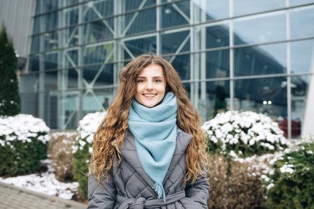 Portrait of beautiful stylish caucasian woman smiling at camera looking confident. Wearing blue scarf, urban city background. Real people. Beautiful charming girl enjoying fashion