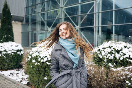 Charming young curly woman with a magnificent brown hair, big brown eyes and stylish look turns to camera and smiles. Attractive young lady is rushing in the winter city-center Фото со стока