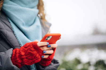 Close up of woman hands texting on smartphone standing on street in winter city on New Year. Female fingers tapping on cellphone outdoors. Modern holidays online shopping, buying new years gifts