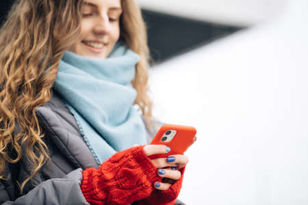 Portrait of cheerful Curly-haired Young female texting on smartphone standing on street in winter city on New Year. Female tapping on cellphone outdoors. Online shopping, buying new years gifts.