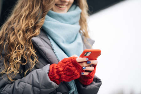 Female fingers tapping on cellphone outdoors. Modern holidays online shopping, buying new years gifts. Close up of woman hands texting on smartphone standing on street in winter city on New Year