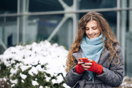 Curly-haired female texting on smartphone standing on street in winter city. Female tapping on cellphone outdoors. Vacation winter outdoor. Happy Young Woman Enjoys Life.