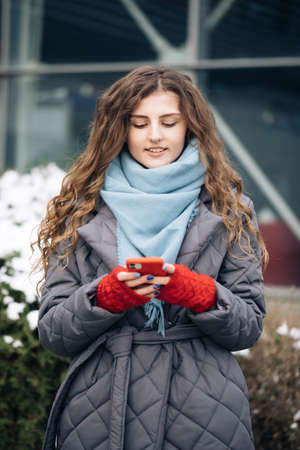 Joyful young female in good mood typing and scrolling on smartphone outdoors. Curly-haired female using smartphone standing outside. A smiling happy girl employee typing on a cellphone.