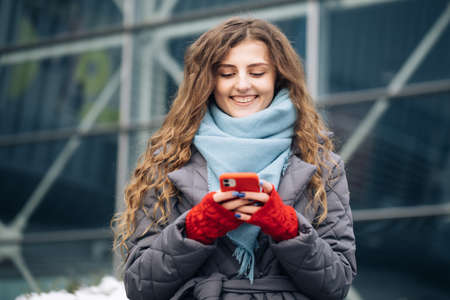 Cheerful Curly-haired Young female texting on smartphone standing on street in winter city on New Year. Female tapping on cellphone outdoors. Online shopping
