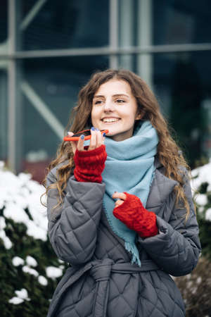 Portrait of Curly-haired Woman with phone using the voice recognition ai audio message on the phone, audio message ai speech helper. Vacation winter outdoor