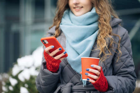Curly-haired Young Girl is Laughing and Reading Something on Her Smartphone While Holding a Cup of Coffee in Other Hand. Woman Walking look around on the street city. Being online, social networks