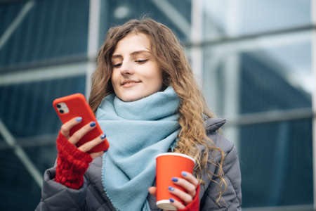 Portrait of happy beautiful curly woman with coffee cup takeaway use mobile phone texting messages. Woman look on the winter street city