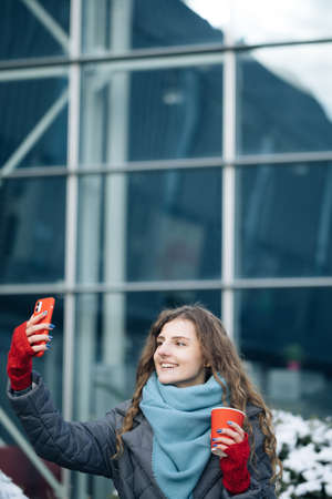 Cheerful woman recording video for vlog in social media or making a video call. Female looking at camera talking with friends and making video conference call record lifestyle blog vlog outdoor