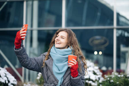 Portrait of happy girl taking selfie holding camera at city street. Modern technology, lifestyle and joyful people concept