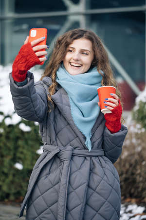 Woman blogger is making video talking for her social page at the street in winter time. Vacation winter outdoor curly girl. Being online, social networks Фото со стока