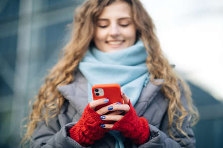 Curly-haired female using smartphone standing outside. A smiling happy girl employee typing on a cellphone. Joyful young female in good mood typing and scrolling on smartphone outdoors