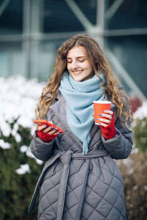 Female portrait. Walking look around on the street city. Being online, social networks. Modern stylish curly woman with cup coffee, uses her smartphone Фото со стока