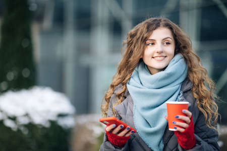 Happy beautiful curly woman with coffee cup takeaway use mobile phone texting messages. Walking look around on the street city.