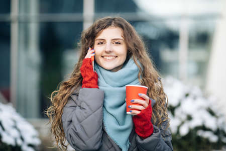 Curly girl talking on her mobile phone while walking in the city street. Curly haired woman using her smartphone and holding red paper cup with coffee. Woman walking and talking Фото со стока