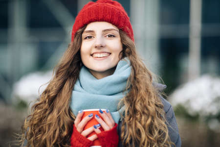 Cheerful gorgeous curly brunette in winter fashion holding coffee cup on urban background. Concept happiness, winter holidays, christmas, beverages and people. Curly female standing on winter street