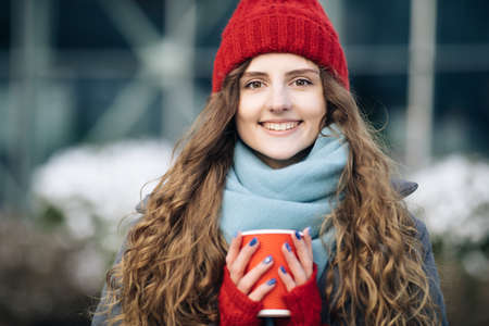 Portrait of nice-looking curly caucasian elegant young woman looking into camera. Female portraits. Girl in a red warm hat with a cup of coffee in her hands stands on the street in winter. Фото со стока