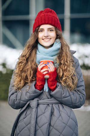 Girl in a red warm hat with a cup of coffee in her hands stands on the street in winter. Portrait of nice-looking curly caucasian elegant young woman looking into camera. Female portraits