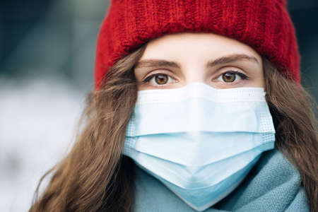 Close up of face calm serious curly haired woman wears protective mask to avoid contaminating coronavirus looks of city background. Health and safety concept. Curly female standing on winter street