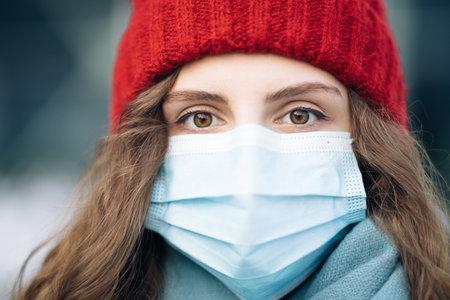 Portrait of Caucasian young curly female in medical face mask standing on winter street. Crowd people sick covid-19. Epidemic coronavirus. Pandemic flu corona virus Фото со стока