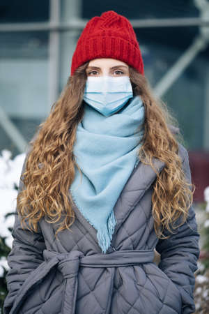 Portrait of a woman with curly hair in the city streets during the day, wearing a face mask against air pollution and Coronavirus Covid19 , looking at camera