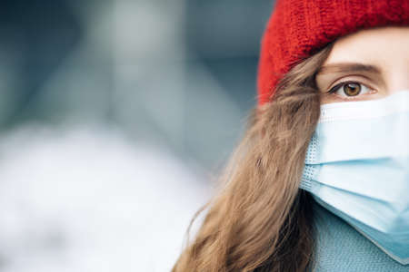 Close up of female half face at street . Portrait of caucasian woman looking at camera. Curly haired woman wears protective mask to avoid contaminating coronavirus. Health and safety concept
