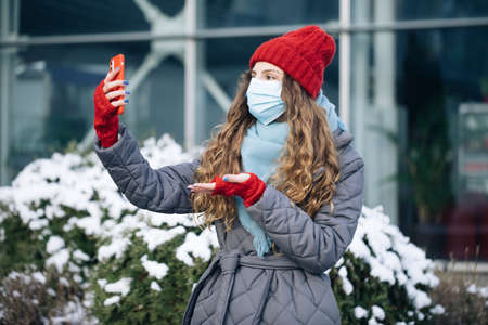 Female blogger in face mask is making video talking for her social page at the street in winter time. Woman look around on the winter street city. Being online, social networks