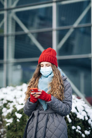 Cheerful Caucasian beautiful curly female in mask browsing on smartphone while standing on street. Joyful young woman texting on cellphone. Curly female standing on winter street