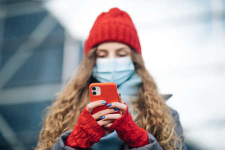 Curly haired woman in protective medical mask walks down to the street uses phone texts scrolls surfs the internet search news covid19 coronavirus virus protection pandemic city. Фото со стока