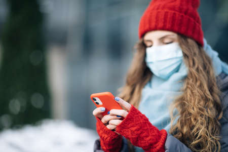 Close up portrait of beautiful Caucasian young curly hair female in medical mask texting on cellphone. Caucasian woman browsing on smartphone and looking away. Being online, social networks. Фото со стока