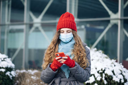 Portrait of Caucasian curly female in mask browsing on smartphone while standing on street. Joyful young woman texting on cellphone. Curly female standing on winter street Фото со стока