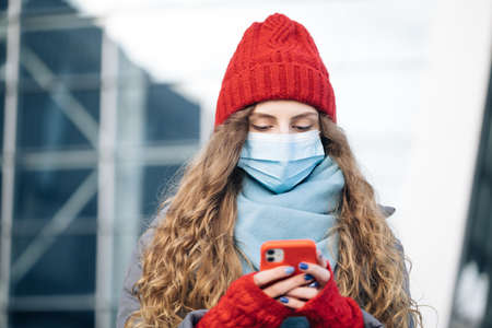 Curly female standing on winter street. Caucasian beautiful curly female in mask browsing on smartphone while standing on street. Joyful young woman texting on cellphone Фото со стока