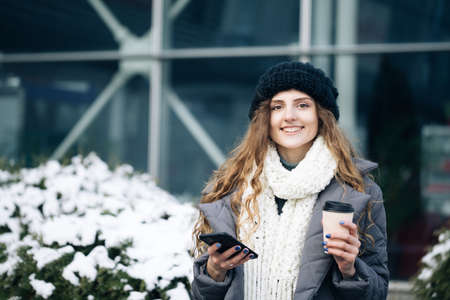 Curly female using smartphone standing outside. A smiling happy girl employee typing on a cellphone. Winter concept. Joyful young female in good mood typing and scrolling on smartphone outdoors