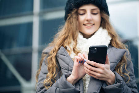 Joyful young female in good mood typing and scrolling on smartphone outdoors. Winter concept. Female using smartphone standing outside. Happy girl employee typing on a cellphone