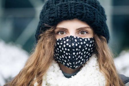 Woman in medical face mask standing against city. COVID-19 Pandemic Coronavirus Woman in a city wearing face mask protective for spreading of disease virus SARS-CoV-2