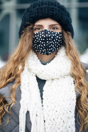 Portrait of a woman with brown curly hair out and about in the city streets during the day, wearing a face mask against air pollution and Coronavirus Covid19, looking at camera.
