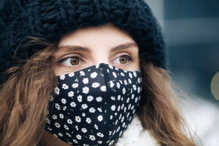 Portrait of a young tourist woman wearing protective face mask on street crowd people. Health and safety, N1H1 coronavirus quarantine, second wave covid virus. Vacation winter outdoor curly girl Фото со стока