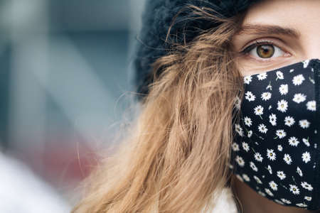 Curly haired woman wears protective mask to avoid contaminating coronavirus. Health and safety concept. Close up of female half face at street . Portrait of caucasian woman looking at camera.