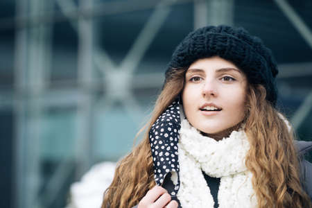 Close up portrait of young woman takes off mask standing at outdoor. Healthcare. Safety measures concept. End of pandemic. Winter outdoor curly girl. Female breathes deeply looking at camera Фото со стока