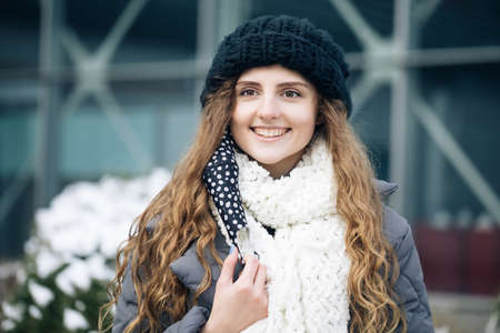 Woman takes off medical mask. Female breathes deeply and smiling looking at camera on city background. Health care and medical concept. Close up portrait curly female standing on winter street