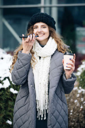 Portrait of Curly haired Woman with phone using the voice recognition ai audio message on the phone, audio message ai speech helper. Vacation winter outdoor Фото со стока