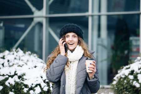 Excited woman winner screaming yes rejoicing success at cellphone. Portrait of young curly woman in winter clothes holding phone celebrate good mobile news surprise bid