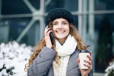 Curly haired woman using her smartphone and holding paper cup with coffee. Young girl talking on her mobile phone while walking in the city street