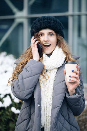 Young girl talking on her mobile phone while walking in the city street. Woman using her smartphone and holding paper cup with coffee