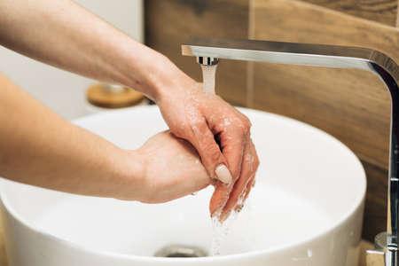 Concept of health, cleaning and preventing germs and coronavirus from contacting hands. Hands of woman wash their hands in a sink to wash the skin and water flows through the hands