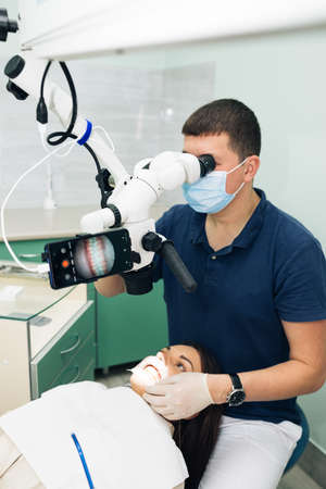 Dentist in latex gloves examining patient teeth in clinic. Patient lying with his open mouth in dentists office. Stomatologist performing examination using a microscope Фото со стока